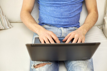 close up of man typing with laptop at home