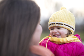 cute little girl in her mother's arm laughing in winter