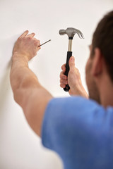 close up of man with hammer hammering nail in wall