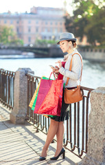 Beautiful girl with shopping bags and mobile phone in the city