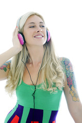 Beautiful blonde woman with tattoos listening music