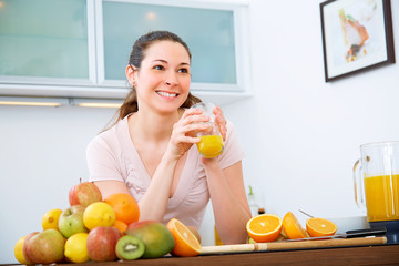 Beautiful woman with orange Juice in the kitchen