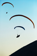 paraglide silhouette over mountains peak