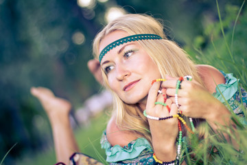 Pensive thoughtful hippie girl is lying on a grass