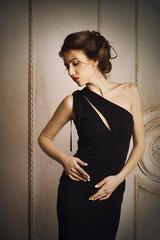 Девушка в чёрном платье с забранными волосами