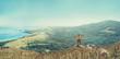 Traveler man standing on peak of mountain near the sea