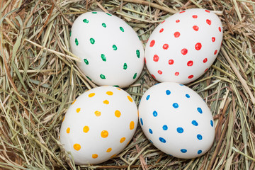 four spotted colored easter eggs in hay