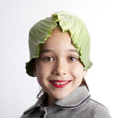 Niña con hojas de repollo por gorro