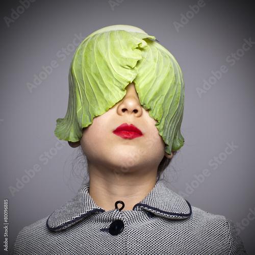 Leinwanddruck Bild Niña con hojas de repollo tapándole los ojos