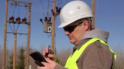 Electrical engineer with tabled PC and cell phone at outdoors