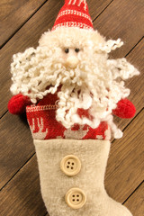 Santa Claus sock with two buttons, christmas decoration on woode