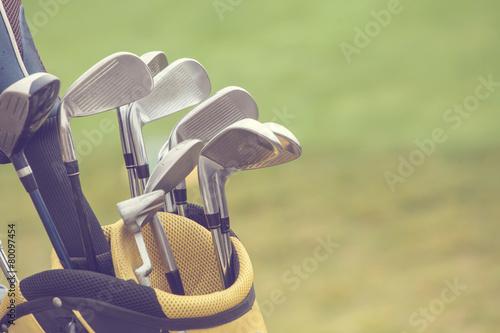 Fototapeta set of golf clubs over green field background