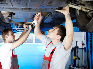 Motor mechanic and apprentice inspecting a car