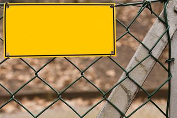 Eine leeres gelbes Schild hängt an einem Maschendrahtzaun
