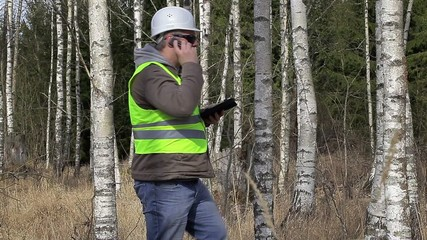Forest engineer talking on cell phone in birch grove