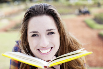 Happy young woman with book outdoors