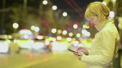 Woman working on tablet in the night city