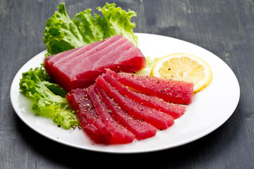 Slices of raw bluefin tuna  sashimi on white dish on wood backgr