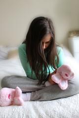 Sad little girl in fluffy slippers