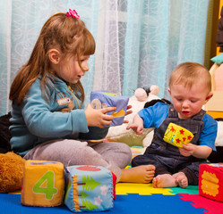 brother and sister playing with soft colored cube