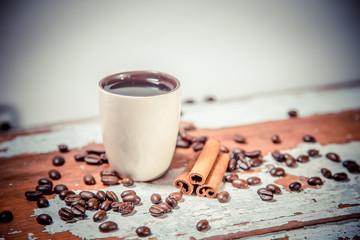 scattered grains of coffee in a cup on a wooden background