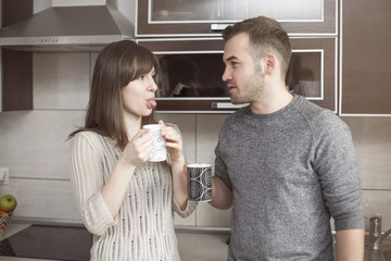 Funny couple joking in kitchen