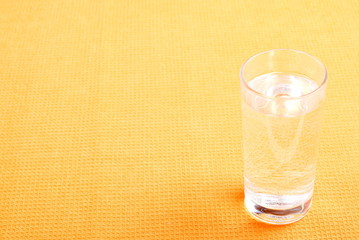 water in a glass and a napkin on the board