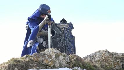 Female Paladin kneeing on rock