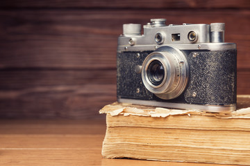 Vintage 35mm film camera on old book over wooden defocused backg
