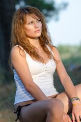 Lady sitting on dead tree, wearing bikini and blouse