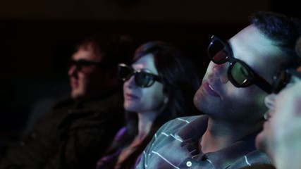 Young man watching a 3D movie with a group of friends, exchanging comments.  Focus on him with a small dolly move and projections on his face.