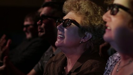 Mature woman applauds as she watches a 3D movie.  Focus on her with a small dolly move and projections on her face.