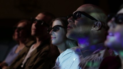 Young man watching a 3D movie with a group of friends.  Focus on him with a small dolly move and projections on his face.