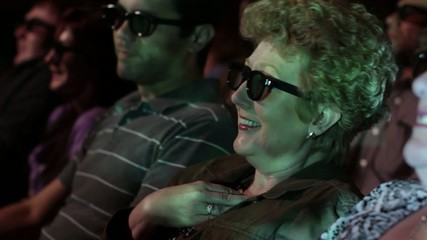 Mature woman gets excited as she watches a 3D movie.  Focus on her with a small dolly move and projections on her face.