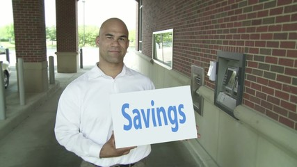 """Man holding card with the word """"Savings"""" which vanishes as he stands next to an ATM.  Camera mounted on jib arm."""