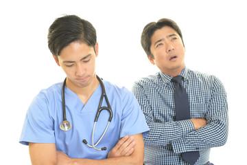 がっかりした表情の医師と患者