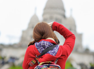 Female tourist taking photo of Sacre-Coeur cathedral