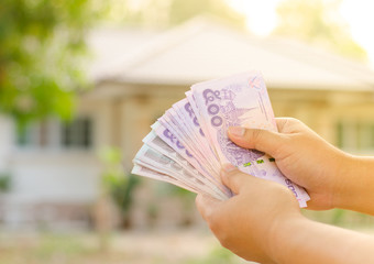 Male hand holding money befor buy house concept