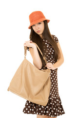 Cute teen girl with purse looking into camera wearing polka dot