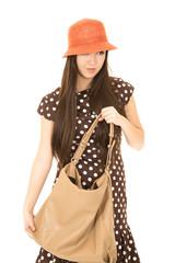 Cute mixed race teen girl holding her purse wearing an orange ha