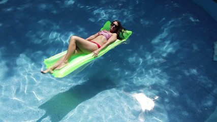 Woman sunbathing on a floating mattress.  Wide shot from above.