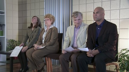 Three interview candidates move away from a fourth, mixed race guy.