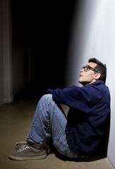 depressed man who lost faith sitting alone in a dark hallway