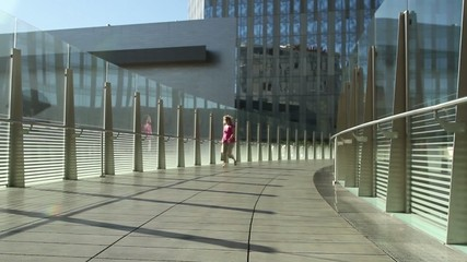 Woman crosses a modern pedestrian bridge, making some happy spins as she goes.