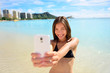 Girl taking fun smartphone selfie on Waikiki beach