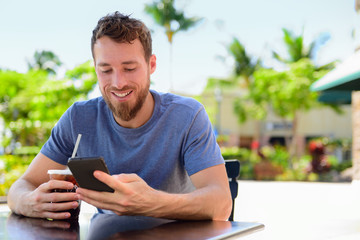 Smartphone man sms texting drinking coffee at cafe