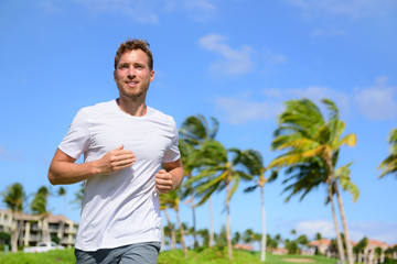 Healthy active man runner running in tropical park