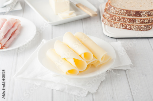 cheese rolled up on white plate - 80111439