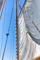 Raising the sail of a tall ship against blue sky. Looking up