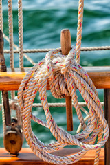 Sailboat deck close up of rope coiled on a wood belaying pin
